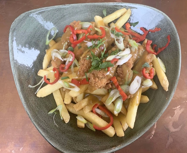 skinny fries in a bowl loaded with katsu chicken curry and chillies