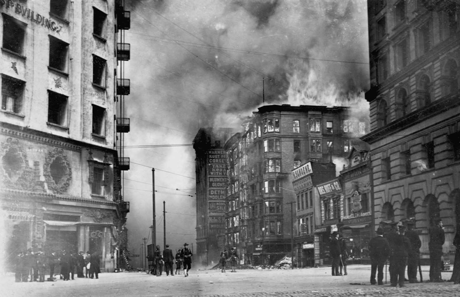 People watch as the Winchester Hotel burns in the aftermath of the 1906 San Francisco earthquake. The Hearst Building (left) was dynamited to use as a fire break between the fire and the rest of the city.