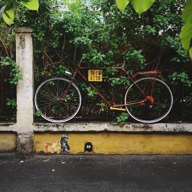 """Chiếc xe đạp – một trong những """"biểu tượng"""" của quán được treo áp vào bờ rào đường sắt"""