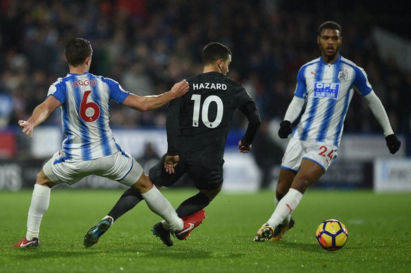 Huddersfield Town's English midfielder Jonathan Hogg (L) fouls Chelsea's Belgian midfielder Eden Hazard during the English Premier League football match between Huddersfield Town and Chelsea at the John Smith's stadium in Huddersfield, northern England on December 12, 2017.