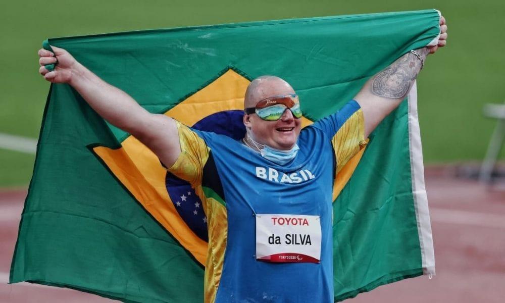 Alessandro Rodrigo está com a bandeira do Brasil e sorri para foto;