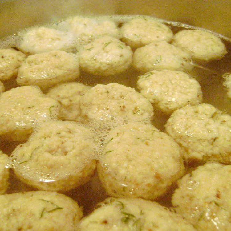 Mini matzo balls boiling in water in a pot for Chicken Soup with Mini Matzo Balls by Renee's Kitchen Adventures