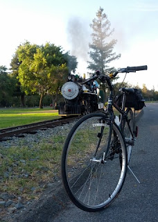 Commute bike poses trackside, with No. 2 steam locomotive approaching.