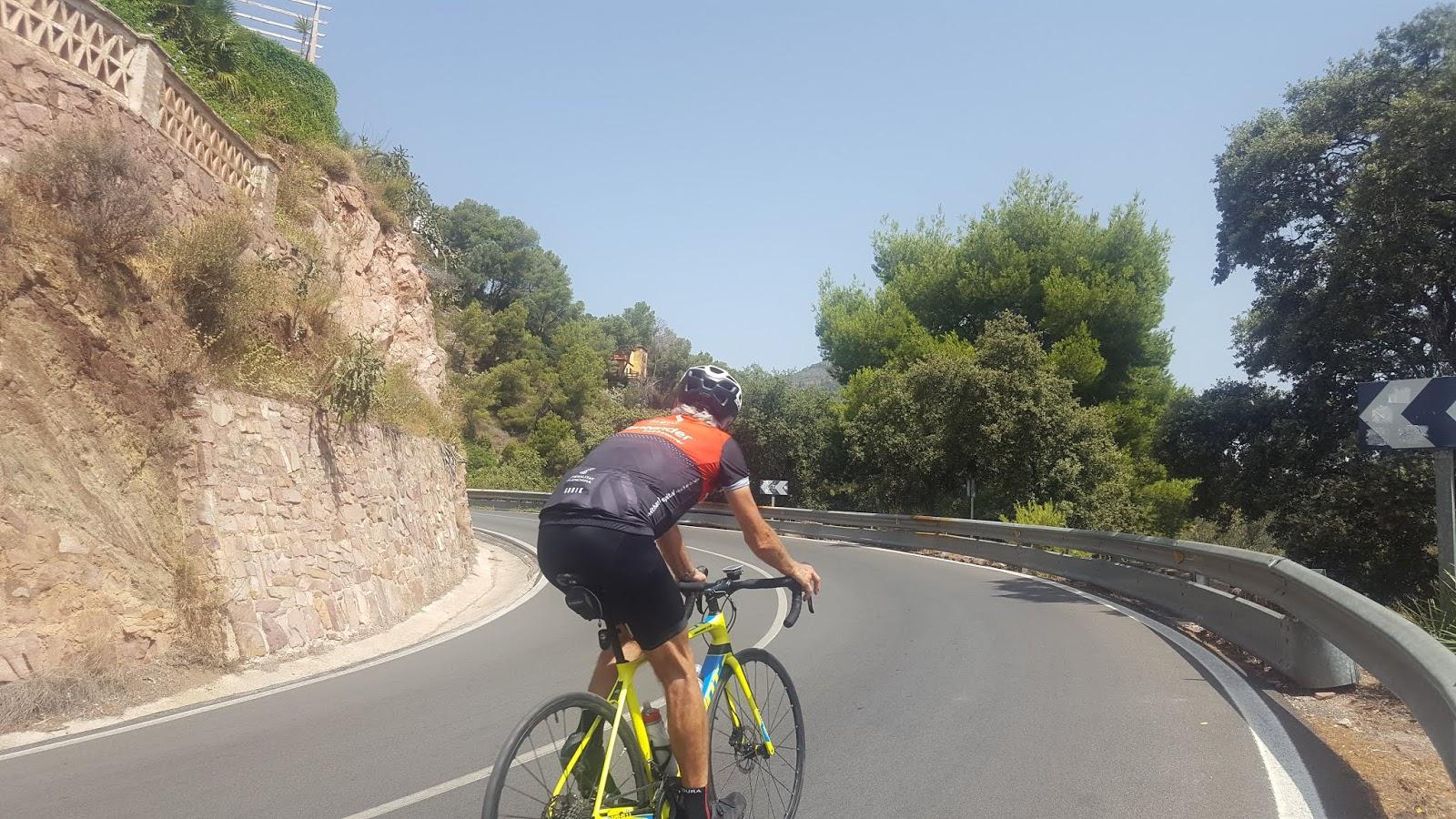 Cyclists climbing Puerto de l'Oronet, Sierra Calderona, Valencia, Spain