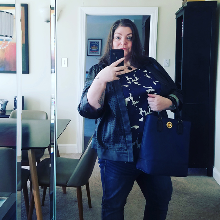 image of me in a mirror, wearing dark blue jeans, a dark blue and black patterened blouse, a black jacket, and a black stone necklace, and carrying a dark blue purse