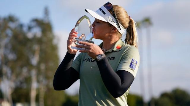 A golfista Brooke Henderson segura e beija seu troféu, em comemoração ao título do Los Angeles Open