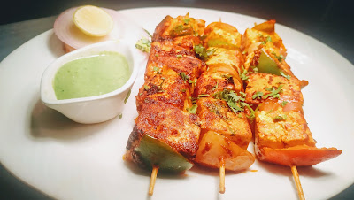 Paneer Tikka with onion and green chutney and lemon wedges using on tawa