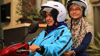 wanita mengendarai motor