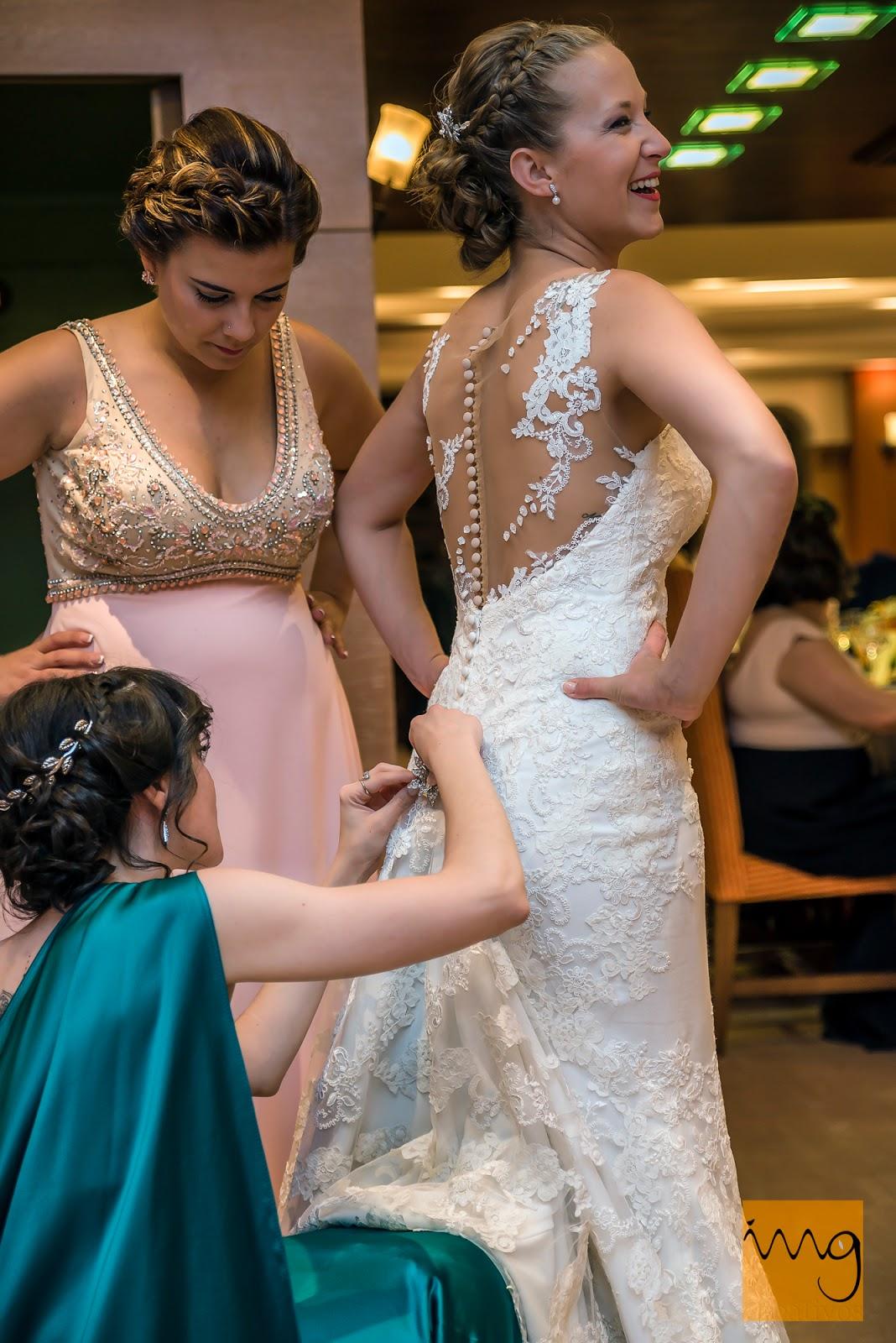 Fotografía de la novia recogiendo la cola del vestido de boda.