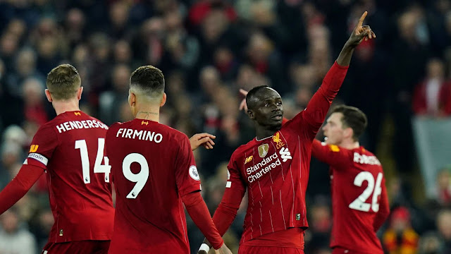 Firmino, Henderson, Robertson celebrate with Mane after scoring the winning goal against Wolves in the Premier League