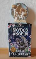 Kirja nojaa seinään, kirjan päällä enkelikoriste