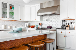 Cozy kitchen with white walls and cabinets and stainless steal appliances