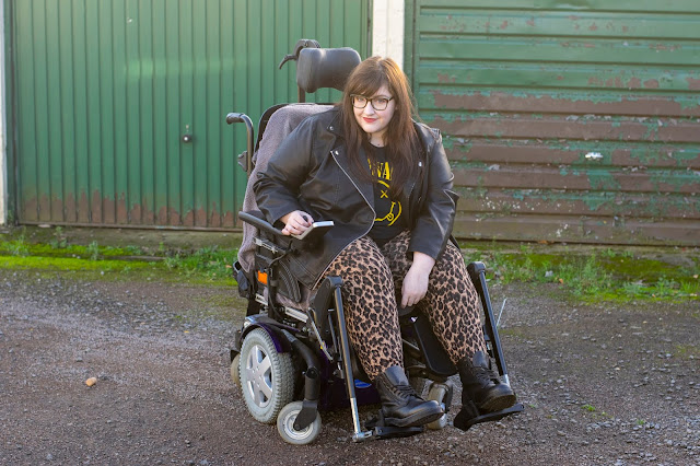 Sarah sat in powerchair with brown hair down wearing leopard print trousers, Dr Martens boots, leather jacket and Nirvana tee