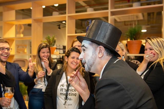Mágico de Humor e Circo apresentando truque onde faz aparecer a carta do convidado dentro da boca, o público assistindo rindo e aplaudindo.