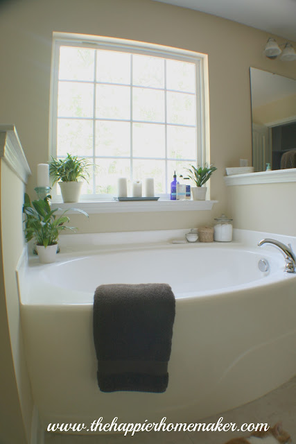 built in garden tub with large window behind it and brown towel draped over the side