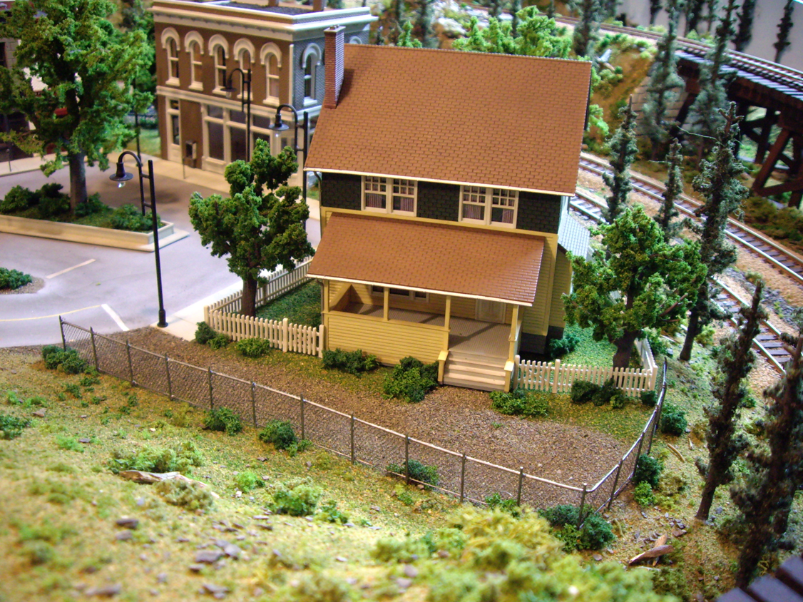 Kate's Colonial Home kit with surrounding scenery including trees and a chain link fence
