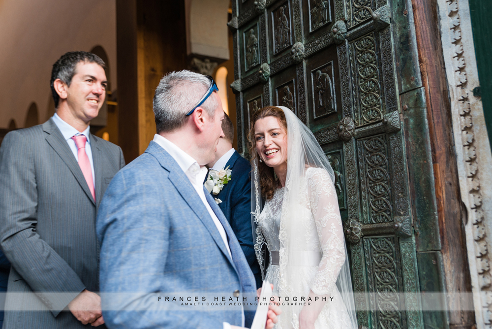 Wedding guests congratulating bride and groom while exiting the church