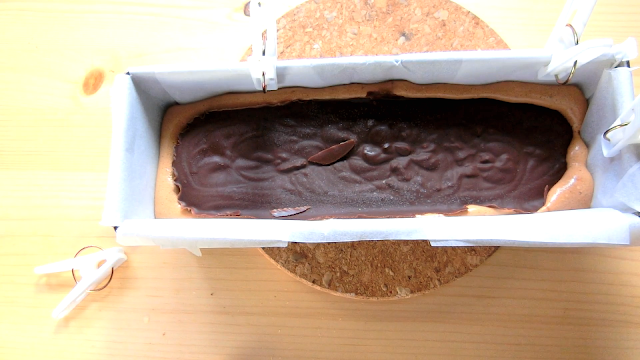 クッキングシートを敷いたパウンド型に生地を流し入れたら凍らせておいた生チョコレートをのせる