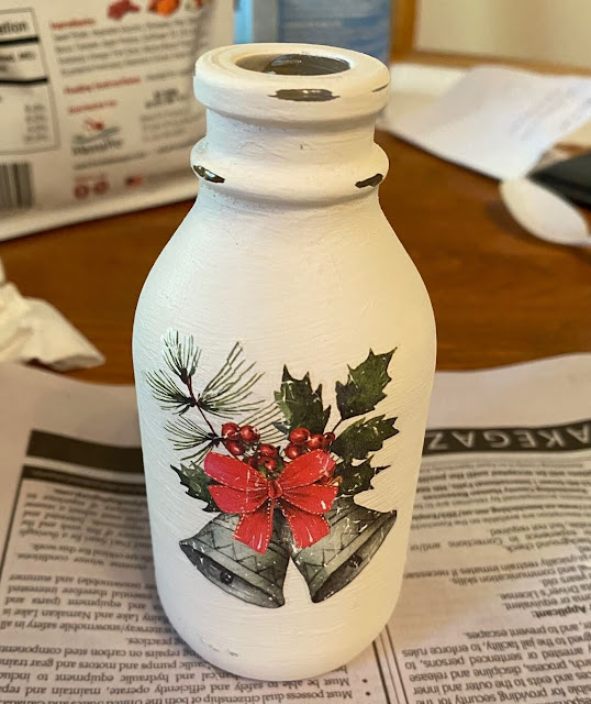 Photo of a chalk painted bottle with Christmas decor transfer design.