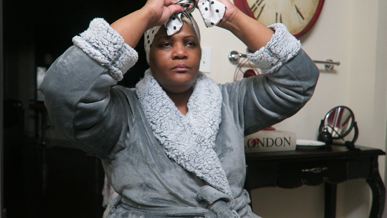 Image: Woman (Tangie Bell in grey robe prepping to do her morning skincare. Shared on Bits and Babbles .Morning Babbles