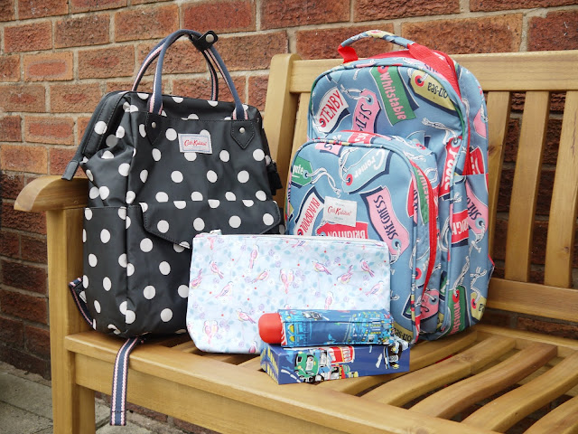 a dark grey backpack with white spots, a blue backpack with multicoloured labels with british seaside names, a smaller pale blue bag, and a dark blue umbrella are clustered on a wooden bench
