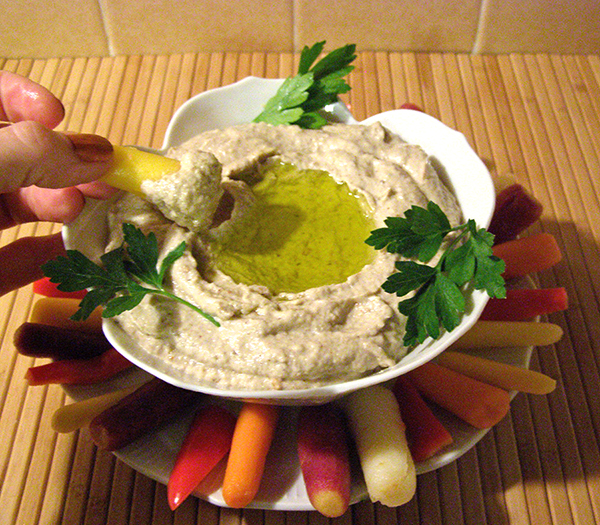 Hand Dipping a Veggie into Baba Ganoush