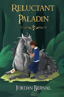 Book cover, 'Reluctant Paladin' by Jordan Bernal. Image depicts a brown-haired, beige-skinned boy kneeling next to a gray dragon, which is lying couchant, with its body resting on its legs. The boy and the dragon are touching foreheads and the boy has the dragon's muzzle between his hands and forearms.