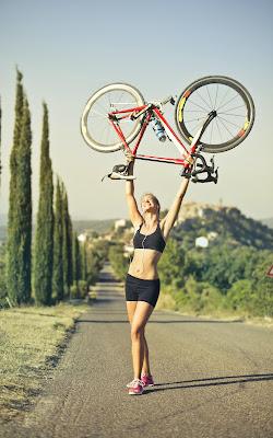 Mujer joven aspecto atletico sostiene una bicicleta en el aire