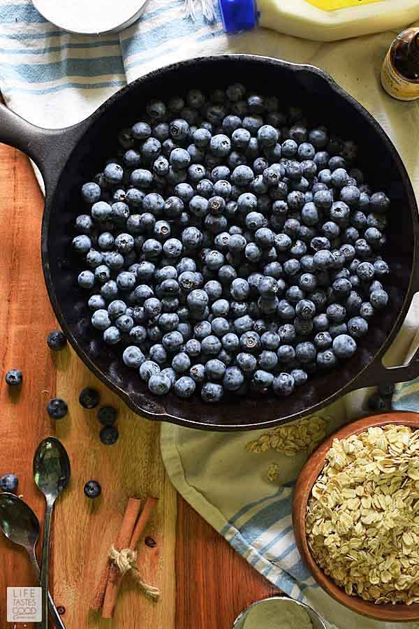 Overhead view of cast iron skillet with 4 cups of blueberries for blueberry crisp recipe