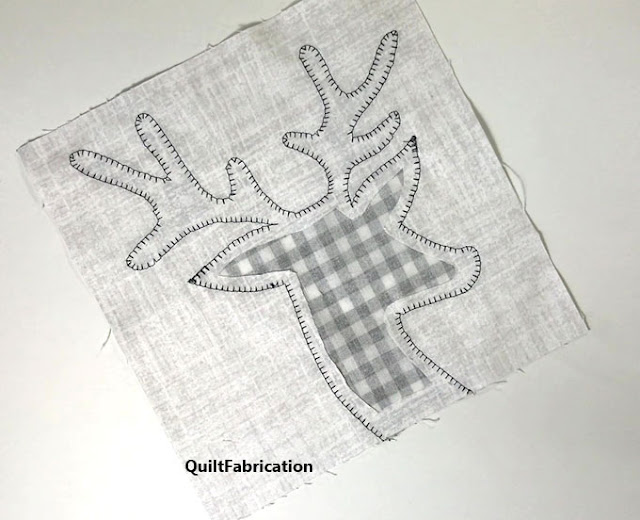 background fabric behind deer head applique being cut out  by QuiltFabrication