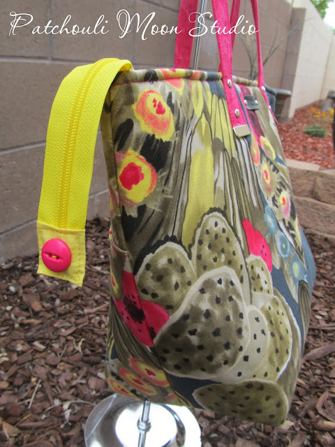 Large tote bag in cactus print and dark fabric sewn on an angle with yellow zipper hanging off side