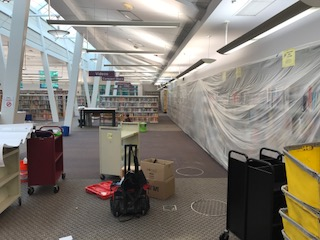 Interior of Quince Orchard Library after renovation preparation begins, such as plastic covering on bookshelves.