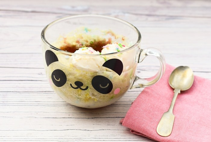 Microwave Jam Sponge Pudding in clear panda mug with pink napkin and small spoon