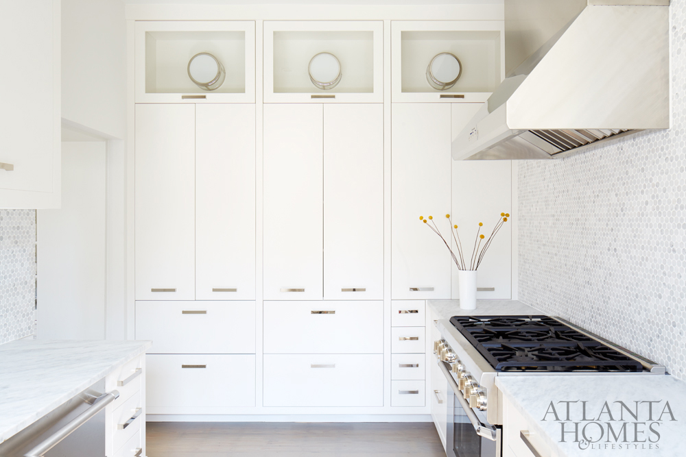 Elegant white kitchen with mosaic tile backsplash and stainless appliances