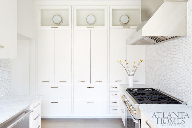 Elegant white kitchen with mosaic tile backsplash and stainless appliances