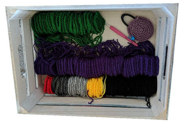 Wooden box with small crochet squares lined up in columns by colour: purple, green, red, yellow, black and grey.