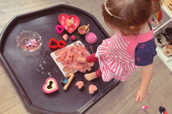 pressing feet into the dough on the Valentine's Day sensory rose playdough tuff tray