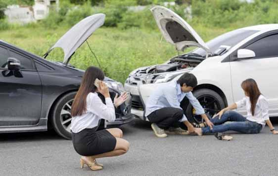 A woman engaged in an accident being attended to by a guy. A woman nearby making a phone call at the accident scene