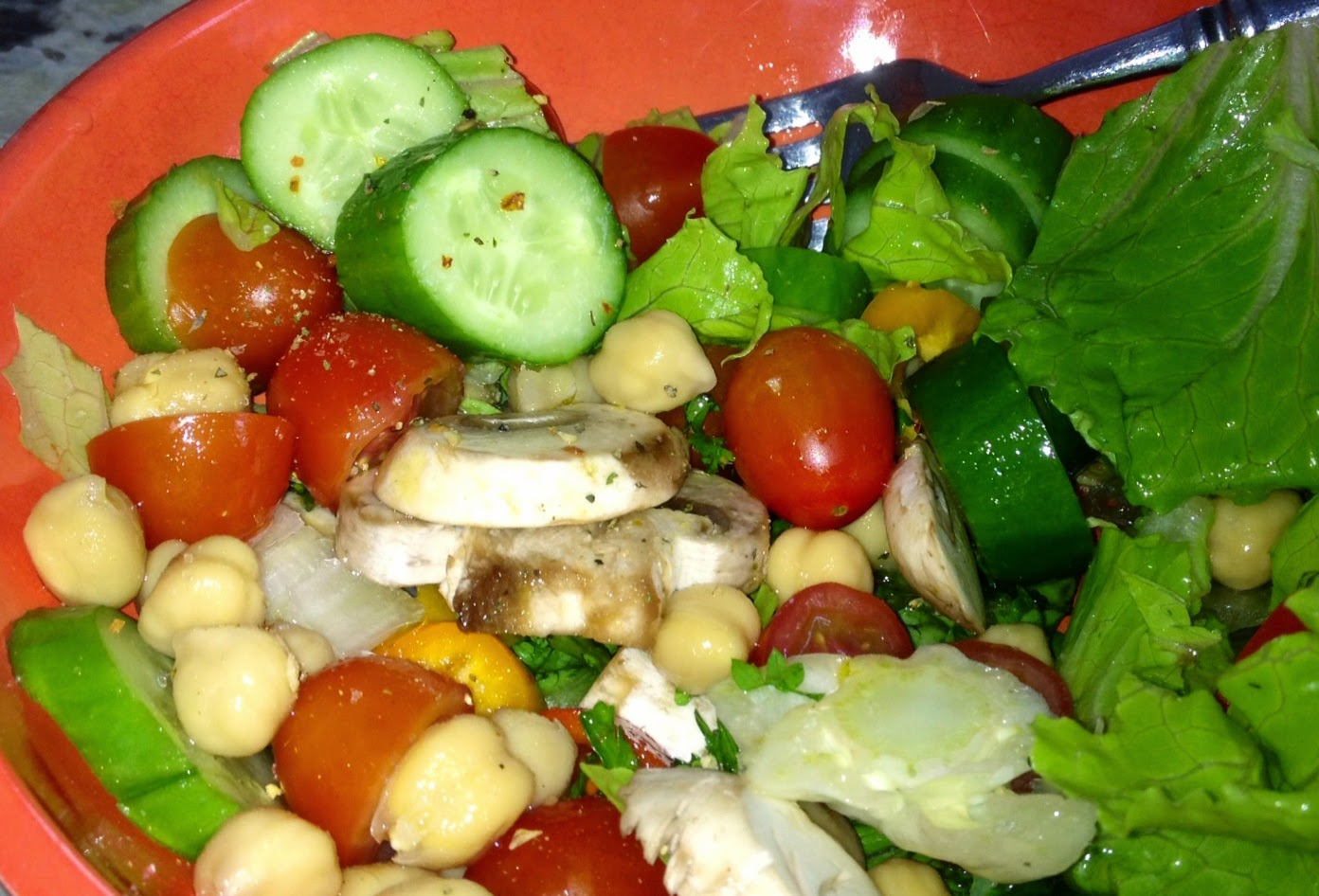 chunks of cut up cucumber, tomato, chick peas, lettuce