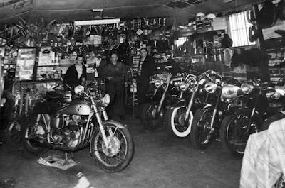 Three men inside motorcycle shop.