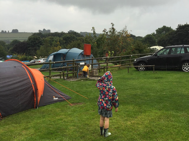 A girl in a waterproof standing next to a tent on a campsite looking at tents