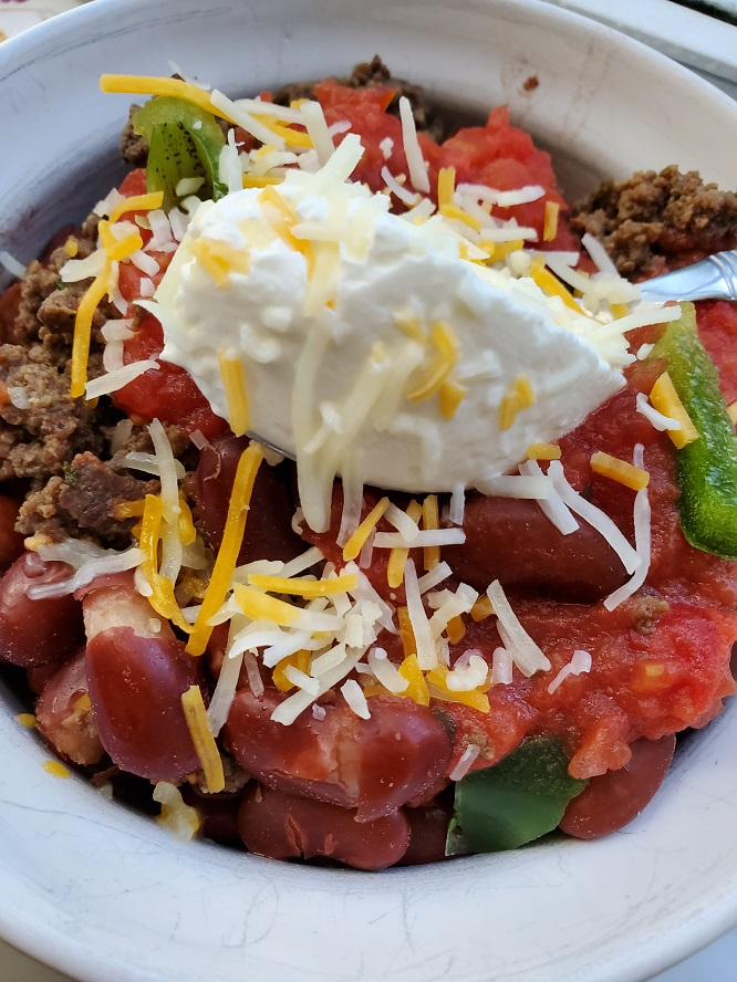 this is a bowl of deer meat made into chili with beans tomatoes and topped with sour cream and shredded cheddar cheese