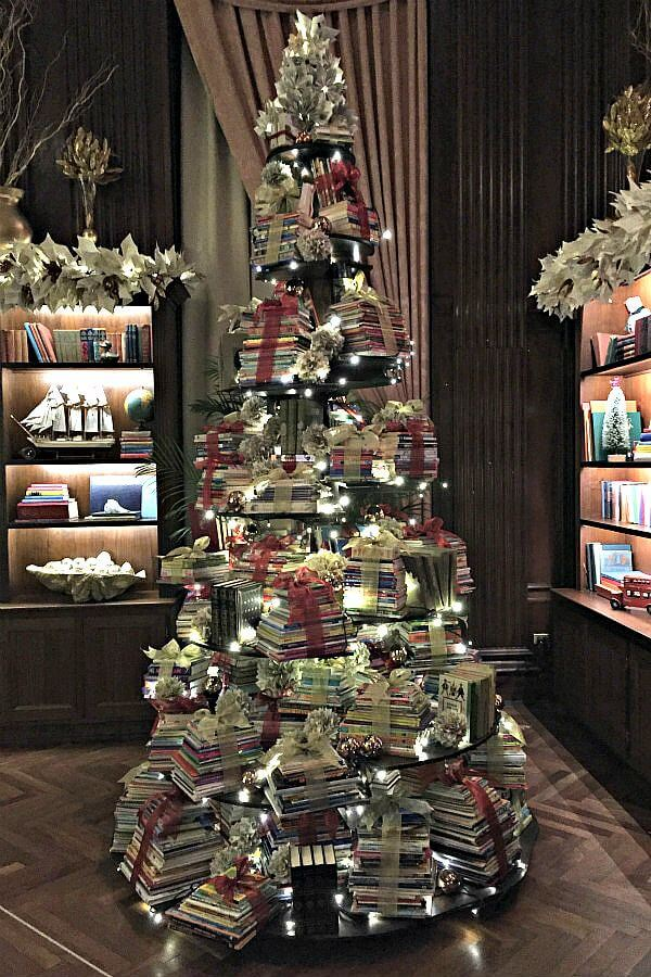 Christmas tree featuring stacks of beribboned books with book page gift toppers