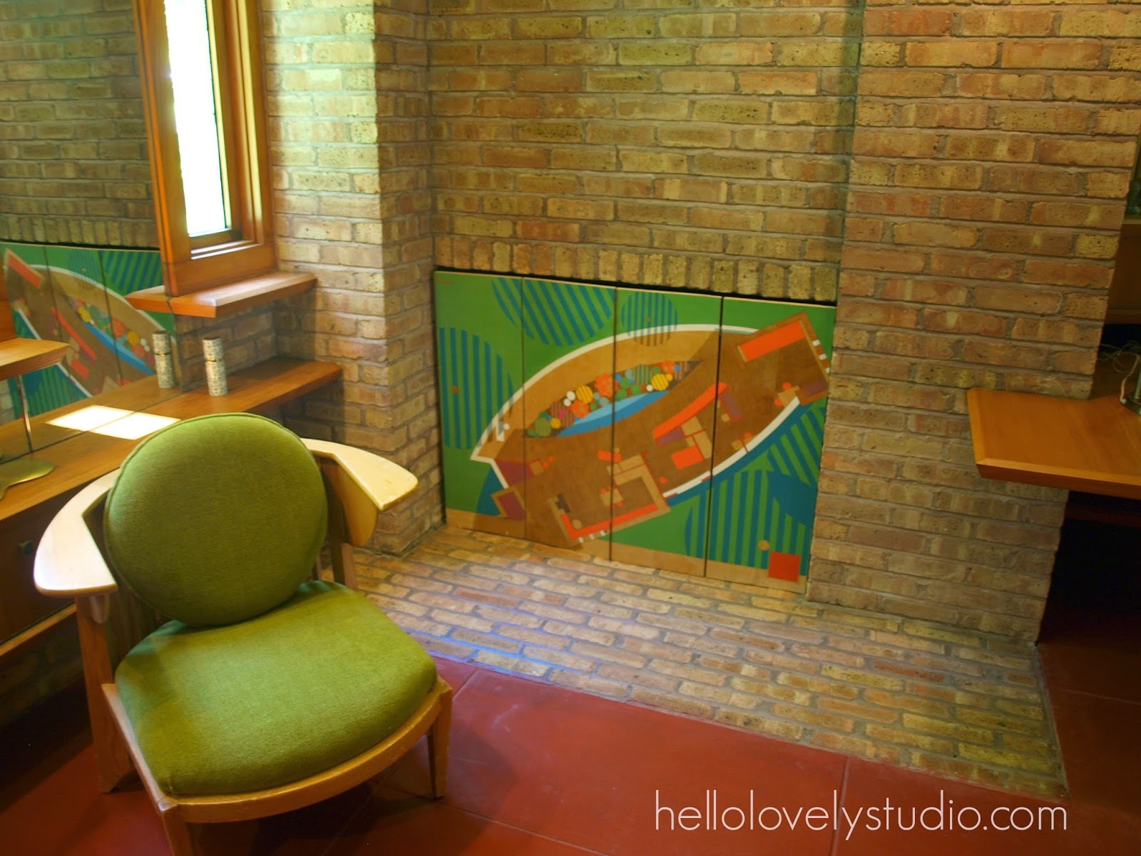 Bedroom with modern custom chair with green upholstery. Frank Lloyd Wright Laurent House designed for owner Kenneth Laurent on Spring Brook Road in Rockford/ Designed to be wheelchair-accessible. #flw #franklloydwrighthouse #midcenturymodernarchitecture