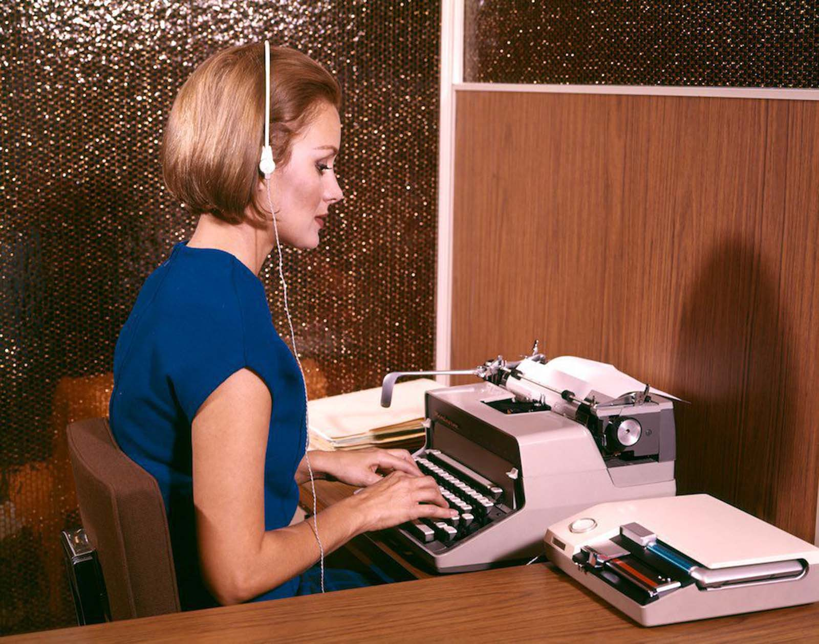 An American secretary typing whilst listening to dictation on her headset. She wears a sleeveless blue top and a blue checked skirt. Her hair is sharply cut and worn chin-length in a brushed bob. 1960s.