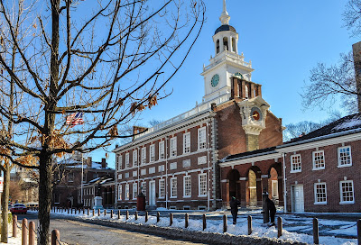 Independence Hall in Pennsylvania in the snow with a leafless tree