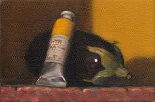 Still life oil painting of a yellow tube of paint resting on an eggplant.