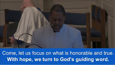 Grace UMC associate pastor, Rev. Levon Sutton, leading the call to worship with displayed litany at the bottom of the screen.