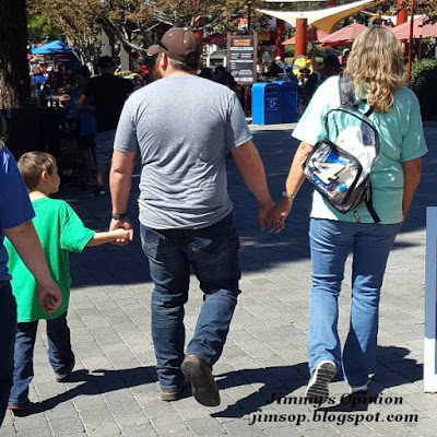 Grandson Benjamin with his Dad Tim who is our son and my wife Cindy all walking together holding hands.