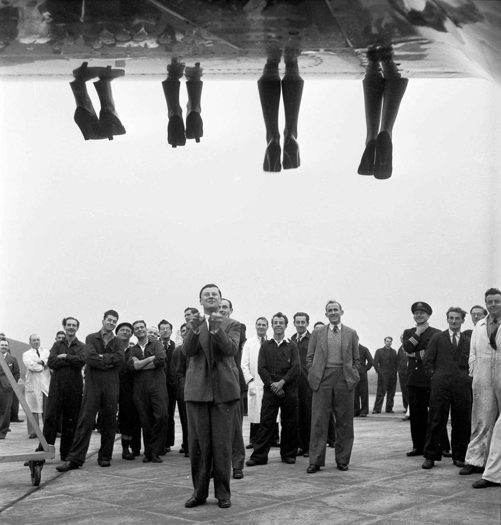The legs of contestants in a 'Miss World' beauty competition dangle over the wing of a BOAC Comet airplane. 1953.